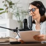 caucasian-millennial-woman-with-a-microphone-and-headphones-recording-a-podcast-in-a-recording-studio